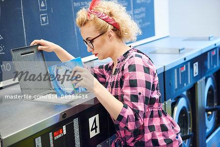 Woman inserting washing powder into washing machine at laundrette