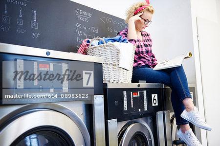 Woman sitting on top of washing machine reading magazine at laundrette