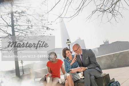 Business people meeting, using digital tablet in sunny urban park, London, UK