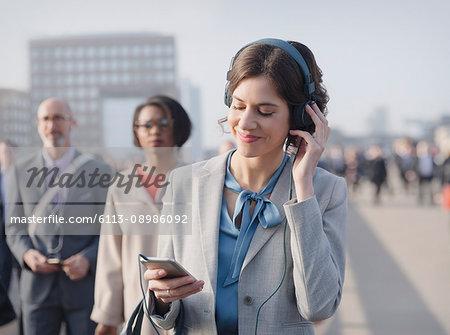 Businesswoman smiling, listening to music with headphones and smart phone on urban pedestrian bridge