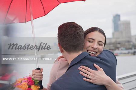 Smiling, affectionate couple with umbrella and flowers hugging on urban bridge, London, UK