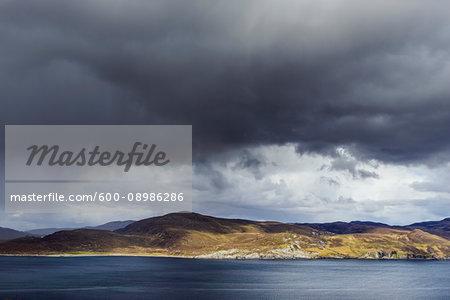 Scottish coast with rainclouds over the Isle of Skye in Scotland, United Kingdom