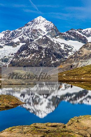 Hiking along a mountain lake reflecting the Swiss Alps near Riffelsee at Zermatt, Switzerland
