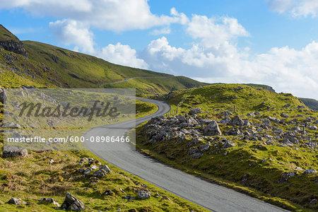 Winding coastal road and typical Scottish landscape on the Isle of Skye in Scotland, United Kingdom