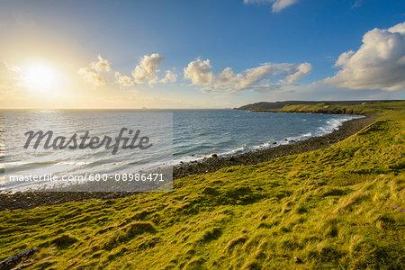 Rocky coastal beach with sun shining over the ocean on the Isle of Skye in Scotland, United Kingdom