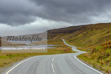 Winding coastal road and typical Scottish landscape on the Trotternish Peninsula on the Isle of Skye in Scotland, United Kingdom