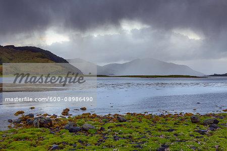 Rainclouds over the grassy shoreline and hills along the Scottish coast near Eilean Donan Castle and Kyle of Lochalsh in Scotland, United Kingdom