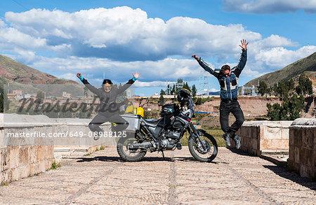 Motorcyclists celebrating on bridge over Urubamba River, Chocosillane Pucara, Cusco, Peru, South America