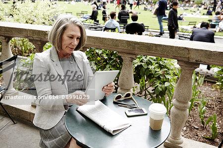 Businesswoman using digital tablet on balcony, New York, USA