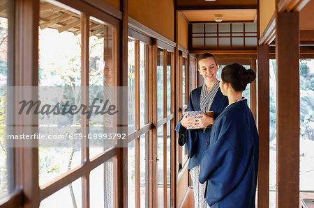 Caucasian woman wearing yukata with Japanese friend at traditional ryokan, Tokyo, Japan