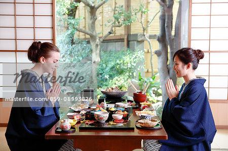 Caucasian woman wearing yukata eating with Japanese friend at traditional ryokan, Tokyo, Japan