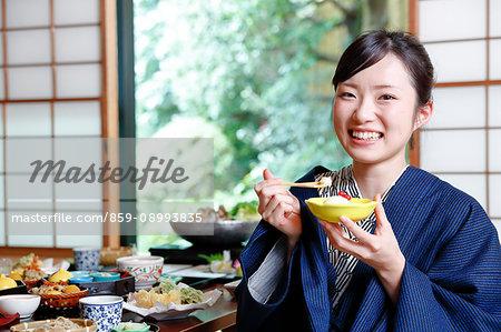 Japanese woman wearing a yukata eating at traditional ryokan, Tokyo, Japan