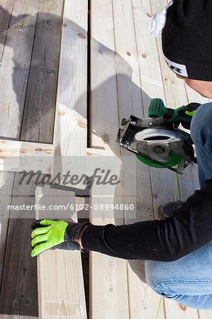 Man cutting plank