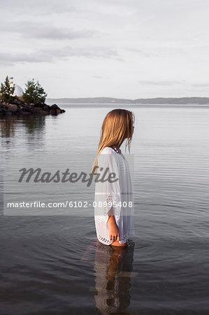 Teenage girl standing in water