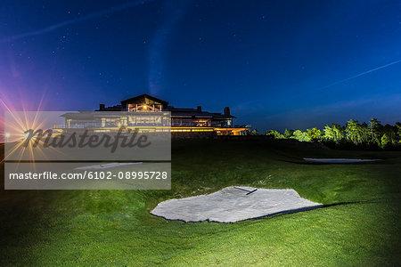 Golf course, illuminated building on background