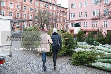 Women walking by Christmas trees