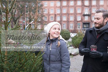 Girl choosing Christmas tree