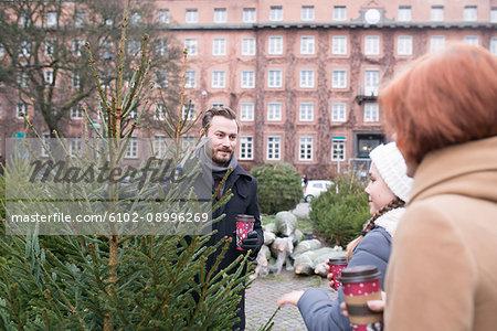 Man and teenage girls choosing Christmas tree