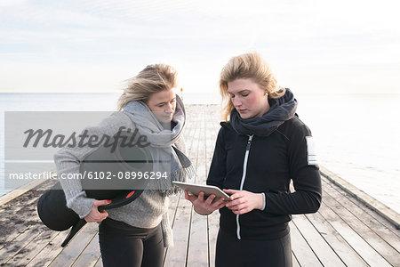 Women using digital tablet on pier