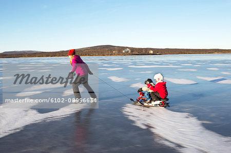 Mother pulling children on sledge