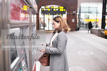 Woman buying ticket in ticket machine