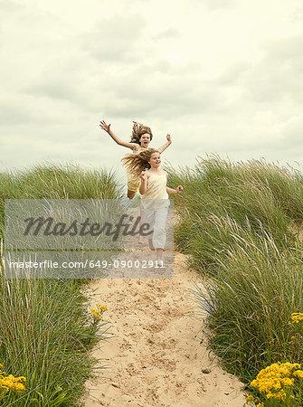 Girls running together on beach