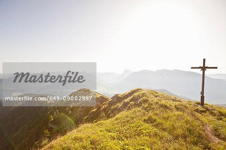 Wooden cross overlooking rural landscape