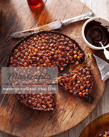Chocolate hazelnut tart on wooden board