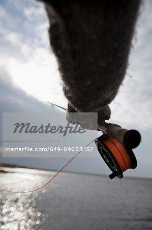 Close up of man using fishing rod