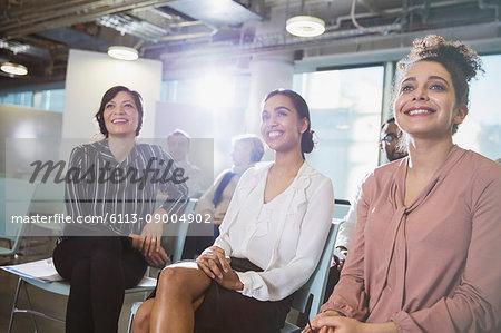 Smiling businesswomen listening in meeting