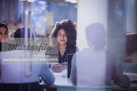 Businesswoman listening in dark conference room meeting