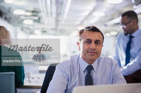 Portrait confident businessman at laptop in office