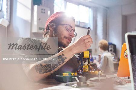 Focused young male designer assembling robotics in workshop