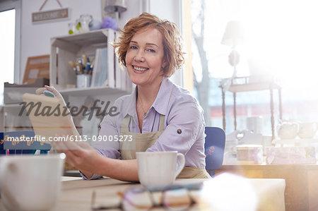Portrait smiling mature female artist painting wood in art class workshop
