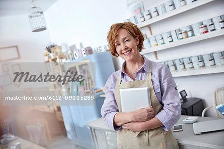 Portrait smiling, confident female business owner holding digital tablet in art shop