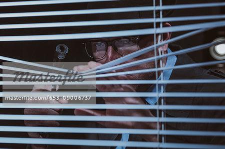 Young man with gun peeking through window blinds