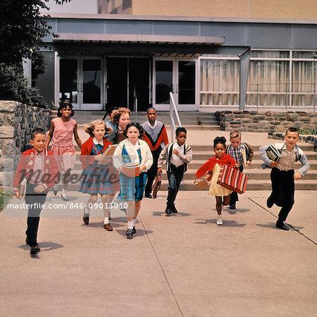 1960s GROUP OF SCHOOL CHILDREN RUNNING DOWN STEPS AWAY FROM SCHOOL BUILDING