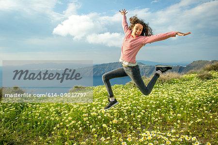Girl jumping over flowers, O'a, Santorini, Kikladhes, Greece
