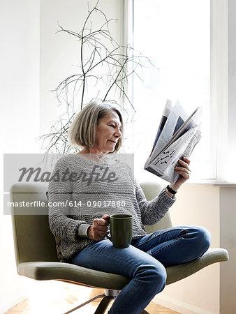 Senior woman with grey bob sitting on swivel chair reading newspaper