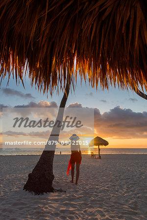 Bavaro Beach, Bavaro, Higuey, Punta Cana, Dominican Republic. Woman by thatch umbrellas on the beach at sunrise (MR).