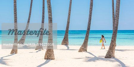 Juanillo Beach (playa Juanillo), Punta Cana, Dominican Republic. Woman walking on the palm-fringed beach (MR).