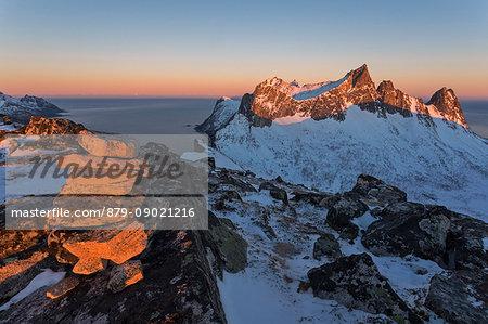 The rocky peaks of the Kongen Mountain and icy sea along the Mefjorden seen from peak Hesten at dawn Senja Tromsø Norway Europe