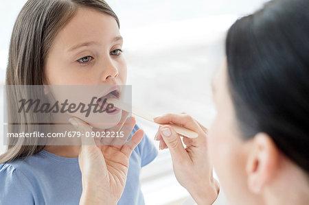 Female doctor examining inside girl's mouth.