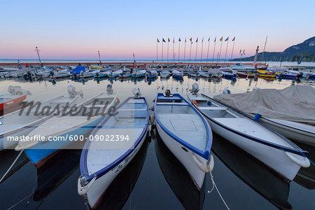 Harbor marina with rows of docked fishing boats Lake Garda (Lago di Garda) at dawn in Garda in Veneto, Italy
