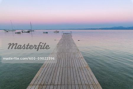 Wooden jetty on the Lake Garda (Lago di Garda) at dawn in Garda in Veneto, Italy
