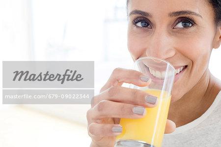 Mid adult woman drinking glass of orange juice, portrait.