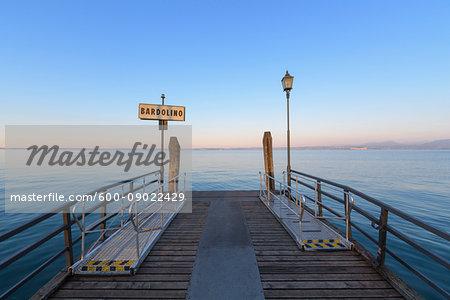 Wooden pier on the Lake Garda (Lago di Garda) at dawn in Bardolino in Veneto, Italy