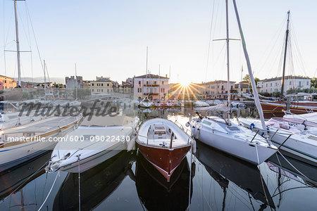 Row of boats in the harbor marina at sunrise on Lake Garda (Lago di Garda) in Bardolino in Veneto, Italy