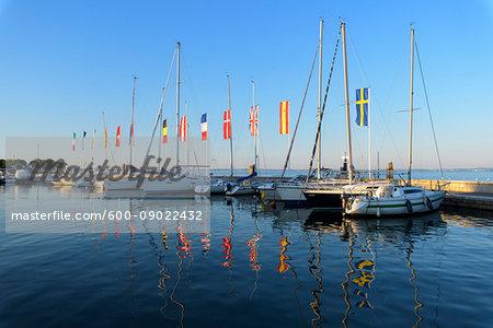 Row of boats and colorful European flags in the harbor marina on Lake Garda (Lago di Garda) at Bardolino in Veneto, Italy