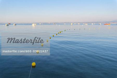 Lake Garda (Lago di Garda) with line of buoys and boats anchored in the distance at Bardolino in Veneto, Italy